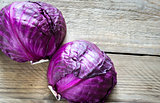Two red cabbages on the wooden background