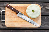Squash on a cutting board  wooden background with  steel knif