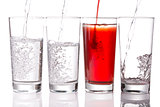 Pouring Squash and Water into Glasses with a black background.