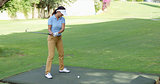 Young female golfer preparing to tee off