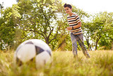Young boy playing soccer game hitting ball