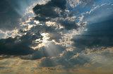 The sun's rays shine through the dark clouds.
