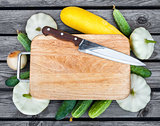 Cutting board, knife, fresh vegetables on wooden table.  Top vie