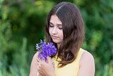 Girl 14 years old looking at bouquet of wildflowers