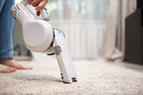 Woman cleaning carpet wireless rechargeable vacuum cleaner