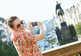 Happy young woman taking photos with digital camera in Prague