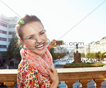 Portrait of happy woman taking photos with cellphone in Prague
