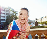 Happy woman with Czech flag showing thumbs up. Prague