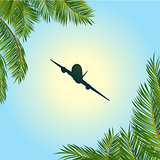 Airplane silhouette over sunny sky and palm trees