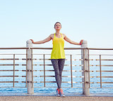 Woman in fitness outfit relaxing after workout at embankment