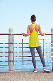 young woman in fitness outfit standing at embankment