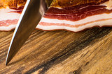 Smoked Bacon on Vintage Wooden Board With a Knife Ready to Cut