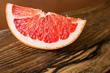 Slice of Red Juicy Grapefruit on Vintage Wooden Board