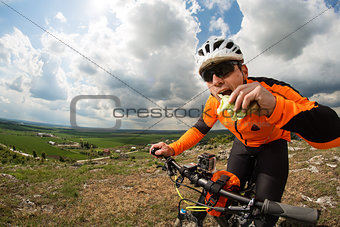 Active man sitting on bike and eating sandwich
