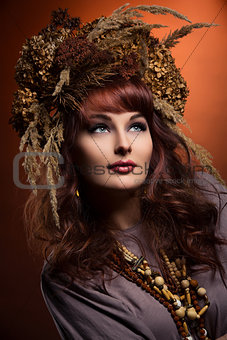 Beautiful young woman with dry flowers on head