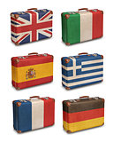 Vintage suitcases with European flags on white