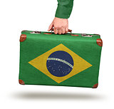 Male hand holding vintage Brazilian flag suitcase