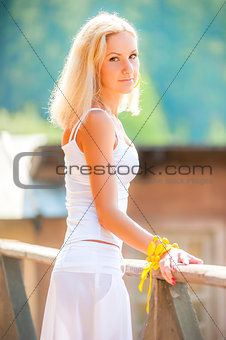beautiful young girl in a white sundress looking at the camera