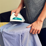 young man ironing a shirt