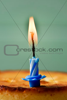 lit birthday candle on a cheesecake