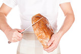 Baker cutting fresh made bread.