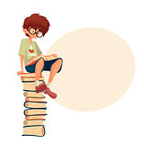 Boy in glasses sitting on pile of books and reading