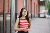 Young Asian woman with glasses hold smartphone in hands.
