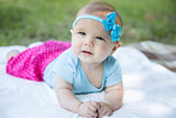 Baby girl crawling on the grass wearing blue bow