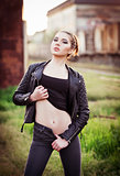 Outdoor fashion shot: beautiful young girl in black jacket, shirt and jeans