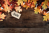 Fall Leaves and Sales Tag over Wooden Background