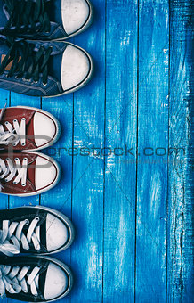 Three pairs of old sneakers on blue worn wooden background