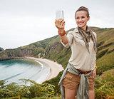woman hiker taking selfie with smartphone in front of ocean
