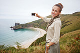 woman hiker taking photo in front of ocean view landscape