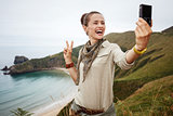 woman hiker taking selfie with digital camera and showing victor