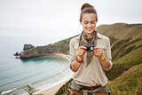 woman hiker viewing photos in front of ocean view landscape