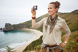 woman hiker taking photo with digital camera