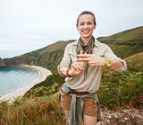 hiker showing hashtag gesture in front of ocean view landscape