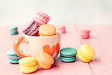 French macarons in cup on pink wooden background.Toned image, vi