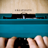 man typewriting the word creativity
