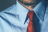 Bearded businessman in blue shirt and red necktie