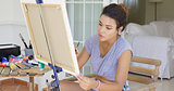 Attractive female artist working on a canvas