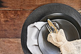Place Setting of Black Dinnerware over Wooden Background