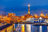 Old Lighthouse in port of Genoa at night, Italy.
