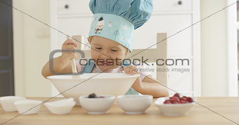 Adorable smiling toddler at mixing bowl