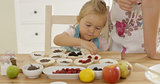 Little girl placing berries on muffins