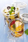 Marinated cheese in glass jar.