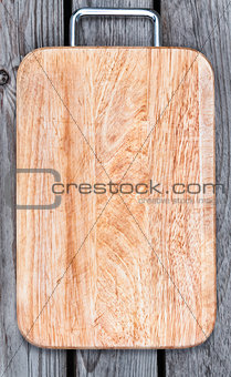Top view of wooden cutting board on old  table