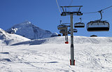 Chair lift in snowy mountains at nice sunny day
