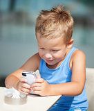 Portrait of blond kid using cell phone