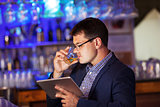 Businessman with tablet drinking whisky in bar